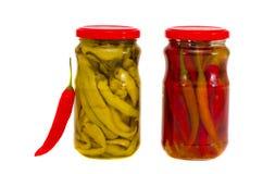 Dois isolaram os frascos de vidro com pimentas vermelhas e verdes Fotografia de Stock Royalty Free