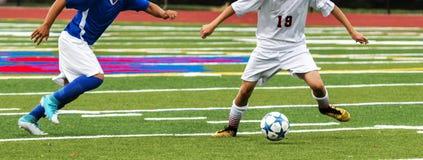 Dois jogadores de futebol da High School lutam pela bola Fotografia de Stock