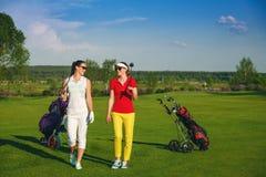 Dois jogadores de golfe bonitos das mulheres que andam no campo de golfe Imagens de Stock