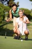 Dois jogadores de golfe fêmeas no campo de golfe Fotos de Stock Royalty Free