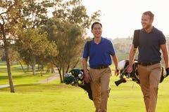 Dois jogadores de golfe masculinos que andam ao longo dos sacos levando do fairway fotos de stock royalty free