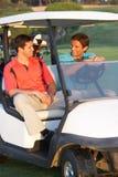 Dois jogadores de golfe masculinos que montam no Buggy do golfe imagens de stock