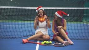 Dois jogadores de tênis das meninas que sentam-se no campo de tênis nos acessórios de ano novo filme