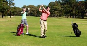 Dois jogadores do jogador de golfe que jogam o golfe junto video estoque