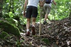 Dois jovens com uma caminhada colam e sapatas durante a caminhada até a montanha na lama Imagem de Stock