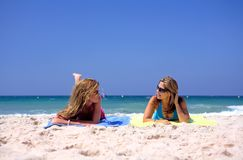 Dois, jovens, mulheres atrativas que encontram-se em uma praia imagens de stock royalty free