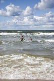 Dois jovens que correm ao mar azul Fotografia de Stock Royalty Free