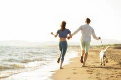 Dois jovens que correm na praia que beija e que guarda firmemente com cão Imagens de Stock