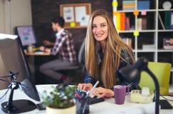 Dois jovens que trabalham em seus computadores, foco na mulher imagens de stock