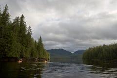Dois kayakers que remam na água calma no dia nebuloso Fotos de Stock Royalty Free