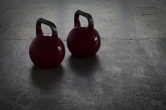 Dois kettlebells vermelhos em um assoalho de pedra em um gym - luz do fundo Foto de Stock Royalty Free