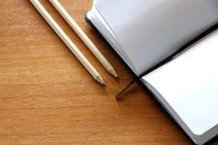 Dois lápis e um caderno aberto em um fundo de madeira foto de stock