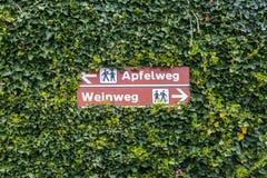 Dois letreiros que guiam caminhantes ao trajeto de Apple, e ao trajeto do vinho, no alemão, no Apfelweg e no Weinweg, em Tirol su imagens de stock