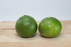 Dois limões verdes em de madeira imagens de stock