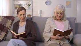 Dois livros de leitura invejosos das mulheres adultas que sentam-se no salão do lar de idosos, rivalidade vídeos de arquivo