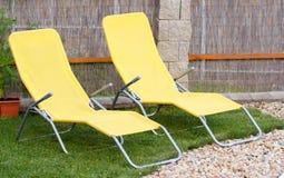 Dois loungers amarelos vazios do sol Fotografia de Stock