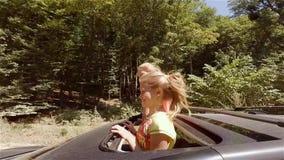 Dois louros novos felizes que riem o pulo fora do portal do carro no movimento contra a floresta filme