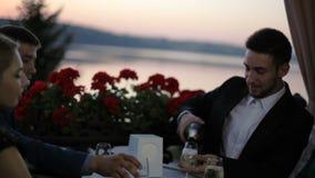 Dois louros vieram em uma data romântica com dois indivíduos em um café do verão no terraço exterior que negligencia o lago video estoque