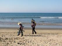 Dois músicos dão uma volta na praia que leva seus instrumentos fotos de stock