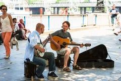 Dois músicos da rua que jogam na terraplenagem de Thames River lon Imagens de Stock
