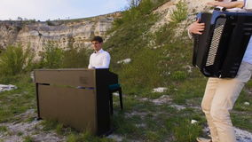 Dois músicos pianista e acordeonista que jogam nas rochas no por do sol sobre o mar filme