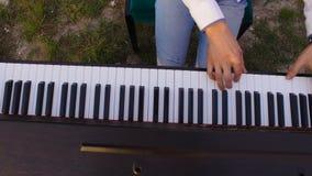 Dois músicos pianista e acordeonista que jogam nas rochas no por do sol sobre o mar video estoque