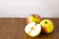 Dois maçã inteira e meio encontro em uma tabela de madeira Fotografia de Stock Royalty Free