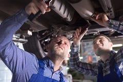 Dois mecânicos de carro na oficina Imagem de Stock