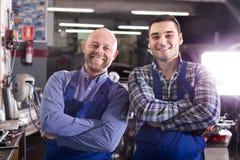 Dois mecânicos de carro na oficina Fotos de Stock