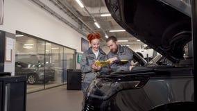 Dois mecânicos de carro profissionais que examinam o motor de um carro, fazendo anotações vídeos de arquivo