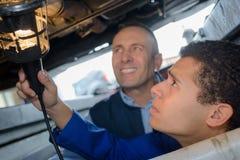 Dois mecânicos que examinam sob o carro na garagem do reparo Imagens de Stock
