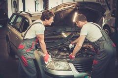 Dois mecânicos que fixam o carro Fotos de Stock Royalty Free