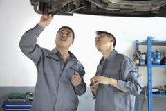 Dois mecânicos que olham o lado de baixo de um carro, discutindo fotos de stock royalty free