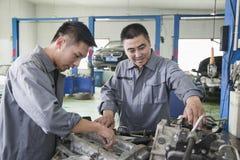 Dois mecânicos que sorriem e que trabalham no motor de automóveis fotos de stock
