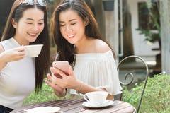 Dois meios sociais do uso autônomo bonito da mulher no smartphone dentro imagens de stock