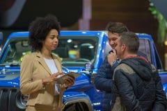 Dois membros do público na discussão com um membro das vendas team fotos de stock