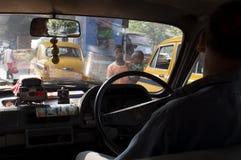 Dois mendigos novos, bebê com acrocephaly, caminhada no tráfego em Kolkata imagem de stock