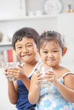 Dois menina e menino cada vidro da terra arrendada do leite Fotos de Stock Royalty Free