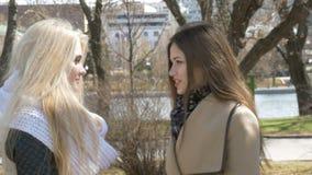 Dois meninas bonitas, louros e morena, falando no parque Alegria, bolsa de estudo e riso video estoque