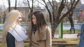 Dois meninas bonitas, louros e morena, falando no parque Encontram seu amigo, um homem novo Alegria, bolsa de estudo e filme