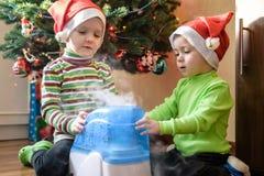 Dois meninos adoráveis que jogam com humidificador de trabalho, x-mas de espera Foto de Stock Royalty Free