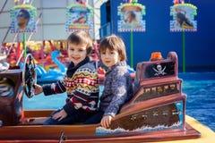 Dois meninos, barco de montada no parque de diversões Fotografia de Stock
