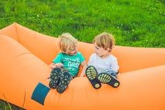 Dois meninos bonitos que descansam em um sofá do ar no parque Fotos de Stock Royalty Free