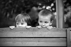 Dois meninos curiosos, olhando sobre uma parede de madeira Fotografia de Stock Royalty Free
