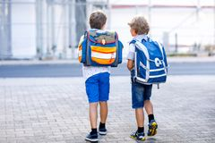 Dois meninos da criança com trouxa ou sacola Alunos na maneira à escola Crianças adoráveis saudáveis, irmãos e fotos de stock royalty free