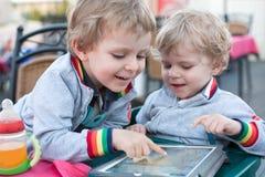Dois meninos da criança do irmão que jogam com PC da tabuleta Fotografia de Stock Royalty Free