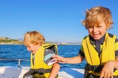 Dois meninos da criança que apreciam a viagem do barco de navigação Fotos de Stock Royalty Free
