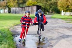 Dois meninos das crianças que montam em 'trotinette's do impulso na maneira a ou da escola Estudantes de 7 anos que conduzem atra Fotografia de Stock