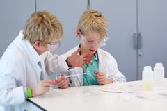 Dois meninos de escola durante a classe de química Fotos de Stock Royalty Free