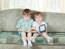 Dois meninos de leitura. Com o livro de papel e eletrônico Fotos de Stock